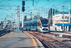 Il treno ad alta velocità arriva sulla stazione ferroviaria al tramonto Immagini Stock Libere da Diritti