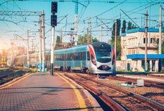 Il treno ad alta velocità arriva sulla stazione ferroviaria al tramonto Fotografia Stock