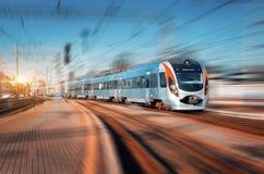 Il treno ad alta velocità arriva sulla stazione ferroviaria al tramonto Fotografie Stock Libere da Diritti