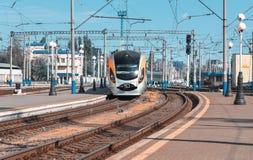 Il treno ad alta velocità arriva sulla stazione ferroviaria al tramonto Immagine Stock