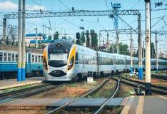 Il treno ad alta velocità arriva sulla stazione ferroviaria al tramonto Immagini Stock