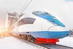 Il treno ad alta velocità guida al ponte ferroviario del metallo ad alta velocità nell'inverno intorno al paesaggio nevoso Immagine Stock