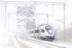 Il treno ad alta velocità guida al ponte ferroviario del metallo ad alta velocità nell'inverno intorno al paesaggio nevoso Fotografie Stock