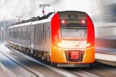 Il treno ad alta velocità guida all'alta velocità alla stazione ferroviaria nella città Immagine Stock