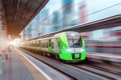 Il treno ad alta velocità guida all'alta velocità alla stazione ferroviaria nella città Fotografie Stock