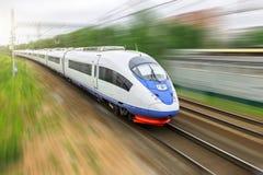 Il treno ad alta velocità guida all'alta velocità alla stazione ferroviaria nella città Immagini Stock