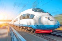 Il treno ad alta velocità guida all'alta velocità alla stazione ferroviaria nella città Fotografia Stock