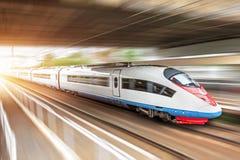 Il treno ad alta velocità guida all'alta velocità alla stazione ferroviaria nella città, tramite un tunnel sotto un ponte Fotografia Stock Libera da Diritti