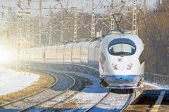 Il treno ad alta velocità guida lungamente al giro all'alta velocità alla stazione ferroviaria nella città Immagini Stock