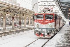 Il treno arriva durante le precipitazioni nevose pesanti nella stazione ferroviaria del nord di Bucarest Fotografie Stock Libere da Diritti