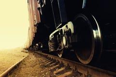 Il treno con una ruota nella priorità alta va oltre l'orizzonte Fotografia Stock