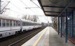 Il treno dei vagoni ad una stazione ferroviaria Fotografia Stock Libera da Diritti