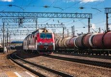Il treno elettrico del passeggero arriva alla stazione ferroviaria della città un giorno soleggiato Vista di prospettiva diagonal fotografia stock libera da diritti