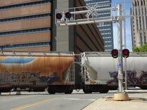Il treno merci commerciale attraversa la strada ad un incrocio di ferrovia Fotografia Stock Libera da Diritti