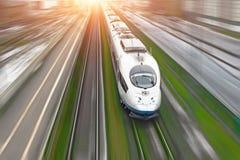 Il treno passeggeri ad alta velocità viaggia all'erba verde della ferrovia ad alta velocità Vista superiore con effetto di moto,  Fotografia Stock