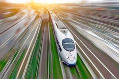 Il treno passeggeri ad alta velocità viaggia all'erba verde della ferrovia ad alta velocità Vista superiore con effetto di moto,  Immagini Stock