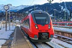 Il treno rosso brillante si è fermato alla st della ferrovia di Garmisch-Partenkirchen Fotografie Stock