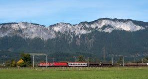 Il treno rosso commerciale viaggia alle alpi austriache Fotografie Stock Libere da Diritti