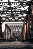 Il treno segue l'attraversamento del Rusty Steel Bridge Fotografia Stock Libera da Diritti