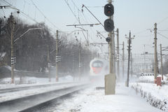 Il treno si precipita nell'inverno nella nuvola della polvere della neve Fotografia Stock