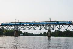 Il treno sta superando il ponte sopra il fiume al tramonto immagini stock