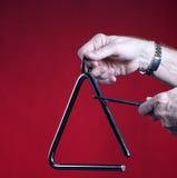 Il triangolo ha giocato isolato su colore rosso Fotografia Stock Libera da Diritti