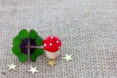 Il trifoglio fortunato, un fungo della mosca e le stelle si trovano su tessuto Fotografia Stock