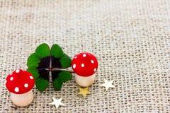 Il trifoglio fortunato, un fungo della mosca e le stelle si trovano su tessuto Fotografia Stock Libera da Diritti