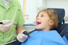 Il trivello stridente della stretta del dentista, ragazza apre la sua bocca Immagine Stock