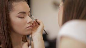 Il truccatore applica l'ombretto, trucco uguagliante perfetto Ragazza della testarossa di bellezza con pelle e le lentiggini perf stock footage