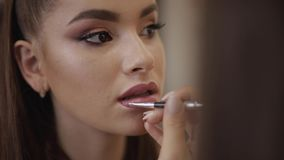 Il truccatore applica il rossetto Mano del padrone di trucco, labbra di verniciatura di giovane modello della testarossa di belle stock footage