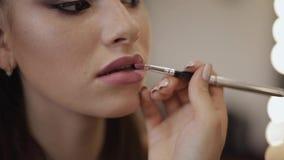 Il truccatore applica il rossetto Mano del padrone di trucco, labbra di verniciatura di giovane modello della testarossa di belle video d archivio