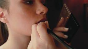 Il truccatore della donna dipinge le labbra di bella ragazza il modello della foto sta preparando per una sessione di foto stock footage