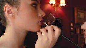 Il truccatore della donna dipinge le labbra di bella ragazza il modello della foto sta preparando per una sessione di foto archivi video