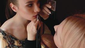 Il truccatore della donna dipinge le labbra di bella ragazza il modello della foto sta preparando per una sessione di foto video d archivio