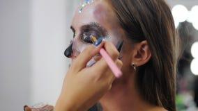 Il truccatore dipinge il cerone per Halloween in studio Donna che estrae un cranio affascinante con i cristalli di rocca e gli ze stock footage