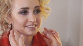 Il truccatore dipinge gli occhi della ragazza con un primo piano della spazzola video d archivio