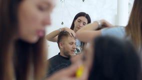 Il truccatore dipinge i cigli di giovane femmina e l'uomo al barbiere guarda dal lato