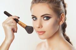 Il truccatore dipinge la polvere sul fronte della ragazza, completa il trucco nel salone di bellezza fotografie stock