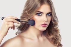 Il truccatore dipinge la polvere sul fronte della ragazza, completa il trucco nel salone di bellezza fotografia stock libera da diritti