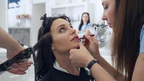 Il truccatore dipinge le labbra del cliente mentre il parrucchiere fa l'acconciatura nel salone di bellezza