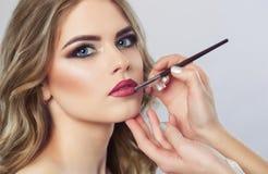 Il truccatore dipinge le labbra di bella donna, completa il trucco nel salone di bellezza immagini stock