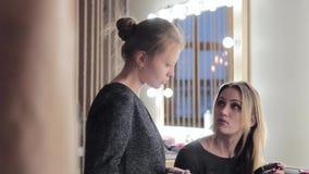 Il truccatore e lo stilista discutono il concetto di trucco prima di photoshoot stock footage