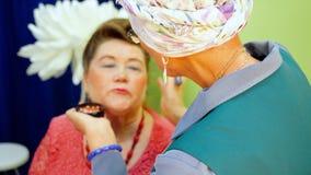 Il truccatore fa l'età Maquillage per la donna senior stock footage