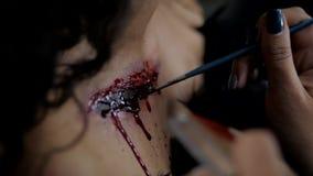Il truccatore fa il trucco di Halloween della ragazza in studio La donna si applica su cerone professionale sul petto della ragaz stock footage
