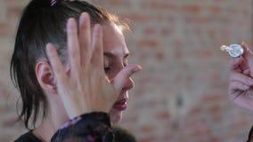 Il truccatore professionista della donna prepara il fronte di giovane ragazza graziosa sveglia per trucco artistico per il cinema stock footage