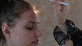 Il truccatore professionista della donna prepara il fronte di giovane ragazza graziosa sveglia per trucco artistico per il cinema archivi video
