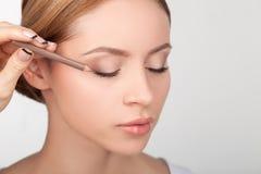 Il truccatore professionista sta dipingendo gli occhi femminili Immagine Stock