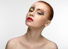 Il trucco ha colorato la pittura sulla ragazza di bellezza degli occhi Immagine Stock