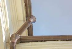 Il tubo del metallo dalla pioggia e neve dal tetto della configurazione Immagine Stock